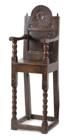 A LATE CHARLES II OAK CHILD'S HIGHCHAIR C.1680 the panelled back decorated with flowerhead