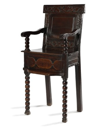 A WILLIAM AND MARY OAK CHILD'S HIGHCHAIR C.1690 the panelled back carved with scrolling tulips and