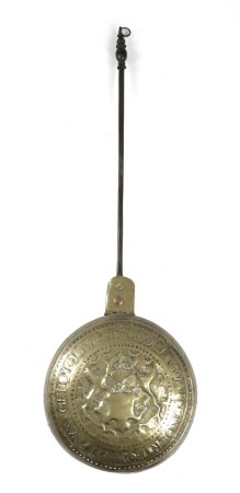 A 17TH CENTURY DUTCH BRASS WARMING PAN DATED 1633 with a turned brass handle and a steel shaft,