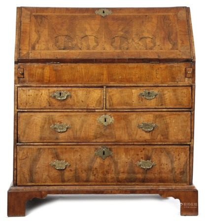 A GEORGE I WALNUT BUREAU C.1715 with cross and feather banding, the hinged fall revealing an