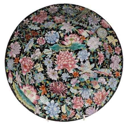 A Chinese famille noire millefleurs charger: painted with lotus, peony,
