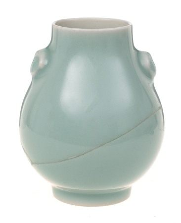 A small Chinese celadon vase: of pear shape with mask head handles and on cylindrical foot,