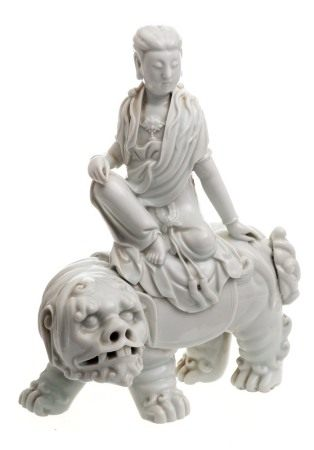 A Chinese Dehua blanc de chine figure group: of a Bodhisattva seated on the back of a Buddhist lion