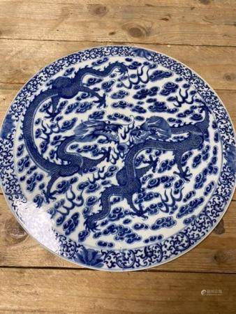 A BLUE AND WHITE CIRCULAR CHINESE PORCELAIN PLAQUE WITH DETAILED CHASING DRAGONS 37CM DIAMETER