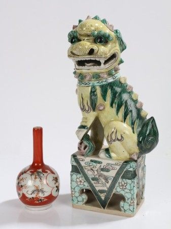 Chinese dog of fo, modelled in a seated position, standing on a pierced foliate and bird decorated