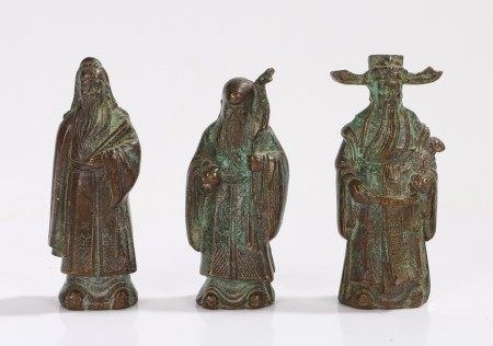 Three Oriental cast metal figures, to include figure holding a stick and orb, 8.5cm high (3)