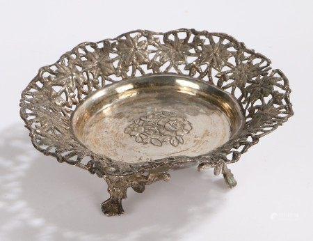 Eastern white metal dish, wih pierced foliate border, raised on three scroll cast feet, 13.5cm