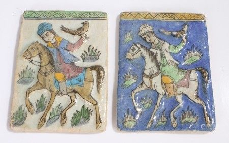 Pair of Eastern tiles decorated with a raised depiction of figure on horseback holding a bird of