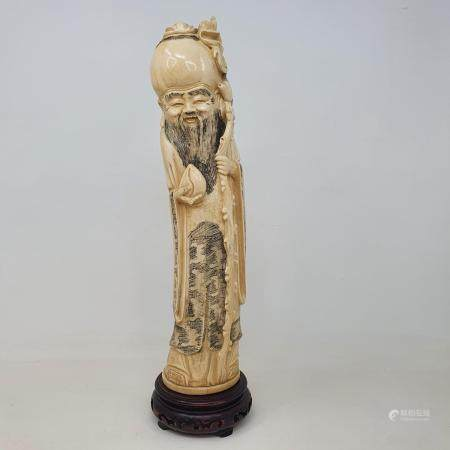 An early 20th century Chinese ivory tusk, carved in the form of Shou Lao, on wooden base, 38 cm