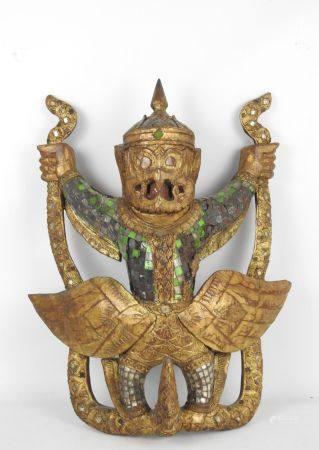 Divinité en bois sculpté doré et incrustations de morceaux de verre. Haut.: 61 cm. Larg.: 52 cm