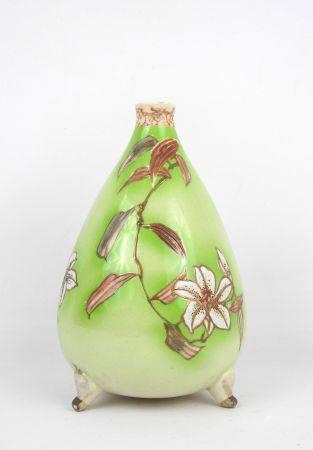JAPON :  Vase piriforme en faïence à décor de fleurs sur fond vert, reposant sur trois patins.