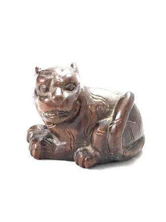 Netsuke en bois, représentant un tigre. Signé Nobuo. Japon, début XXe siècle. L. 4 cm