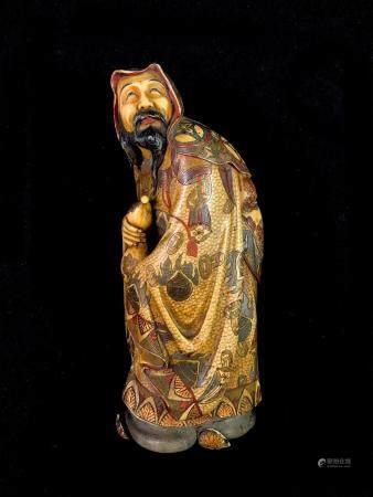 Un okimono en ivoire polychrome representant un sage chinois tenant une gourde, vêtu d'une robe