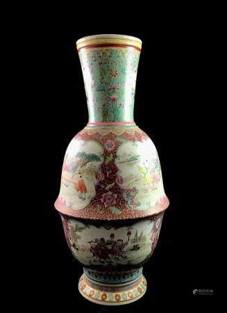 Grand vase en porcelaine à décor en émaux de la famille rose sur un fond rouge parsemés de lotu