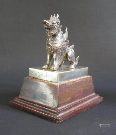 A Burmese White Metal Chinthe standing on a wooden plinth, the base labelled Coombes Company Ltd.