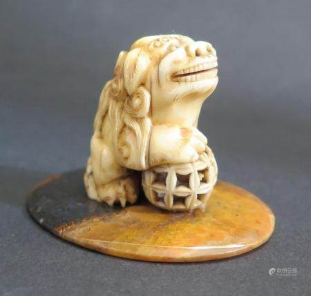 An Antique Chinese Carved Ivory Foo Dog on a polished agate base, 38mm high