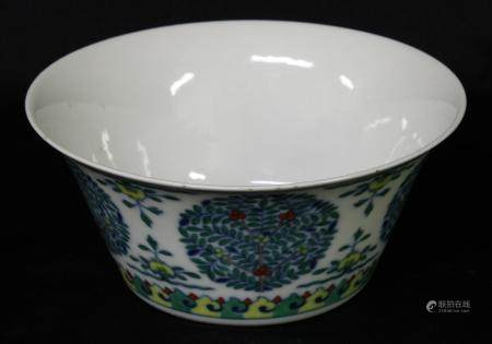 A Chinese wucai flared bowl, painted with stylised trees, flowers and scroll lappets, 16cm diam,
