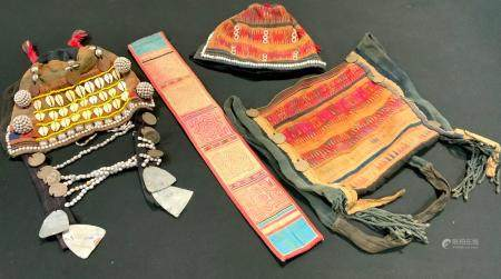 A Tibetan textile hat, of traditional form, elaborately applied with shells, beads, Victorian and