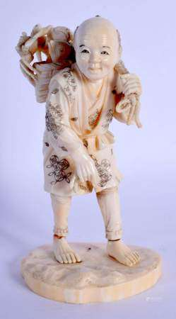 A 19TH CENTURY JAPANESE MEIJI PERIOD CARVED IVORY OKIMONO modelled as a roaming fisherman. 13.5 cm h
