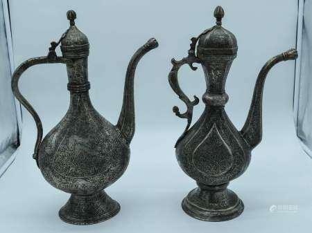 Two Middle Eastern metal embossed Ewers