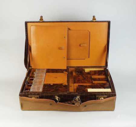 An early 20th century crocodile vanity case