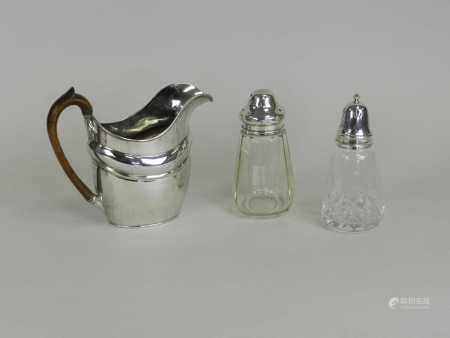 A silver plated jug and two silver mounted glass sugar casters