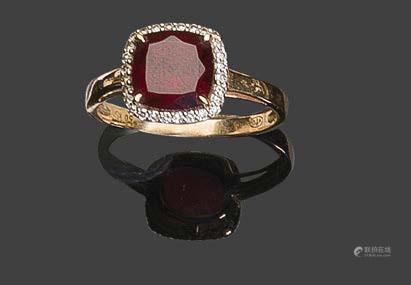 - Bague en or jaune 750°/°°, sertie d'une pierre rouge dans un entourage de petits brillants.Pb