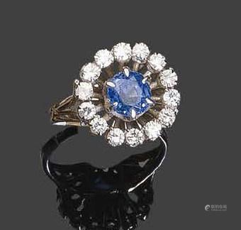 - Bague en or blanc, sertie d'un saphir rond facetté dans un entourage de petits diamants ronds