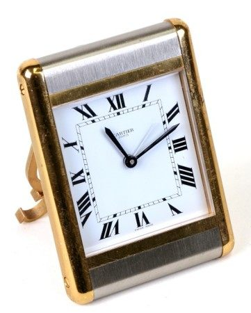 A Cartier brushed steel and brass travel alarm clock, 7.5cms (3ins) wide.Condition Reportsome