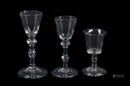 A group of three various light baluster wine glasses