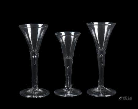 A group of three plain stemmed wine glasses of drawn trumpet form