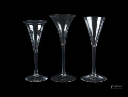 A group of three plain stemmed toasting glasses of drum trumpet form