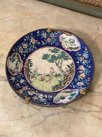 Chine, XIXème siècle.  Plat en cuivre émaillé à décor de personnages dans un jardin dans le méd