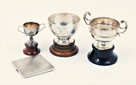 Three silver trophy cups and a silver cigarette case, the trophy cups of varying form and size,