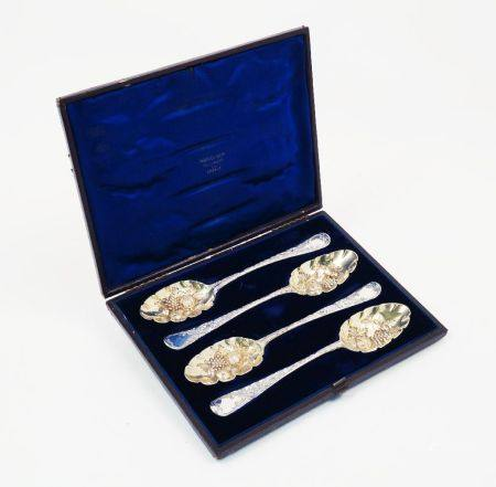A cased set of four matched berry spoons, spurious marks, assumed silver, the repousse gilded