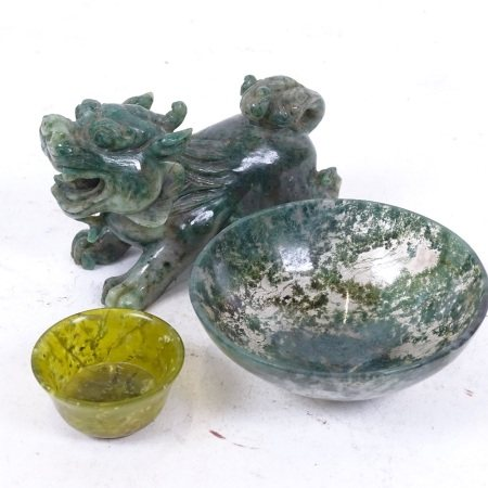 A Chinese miniature carved and polished jadeite temple dog, a moss agate bowl, and another (3)