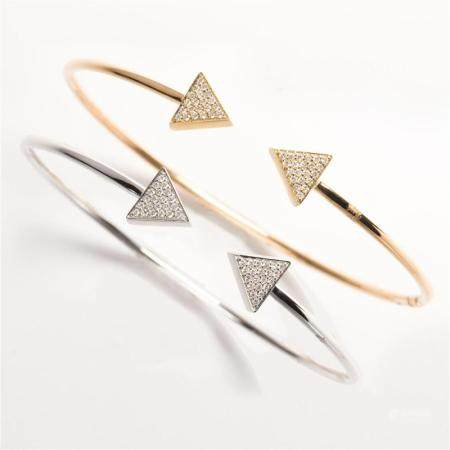 A pair of white or yellow fourteen karat gold and diamond cuff bracelets