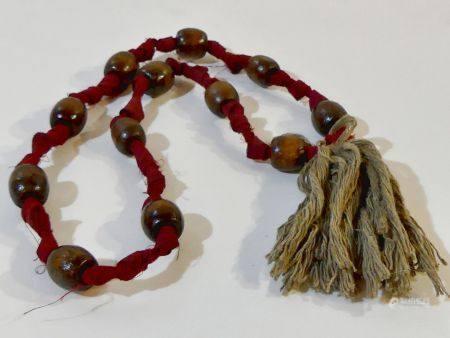 Intéressant chapelet composé de 12 perles en bois enfilées sur un ruban en coton noué provenant