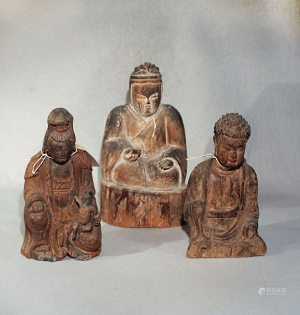 Three Chinese carved wood seated figures, two of a Buddha, the other of Guanyin with child,