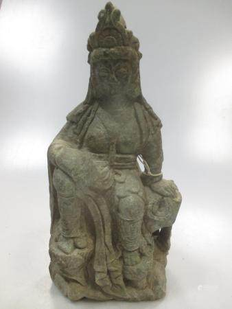 A Chinese carved green stone figure of Gyanyin, in Tang style, seated on a rocky dias, 28cm high