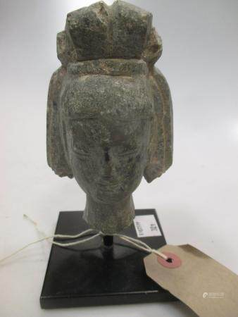 A grey stone head of a Bodhisattva, 11cm high (14cm high to include the stand)
