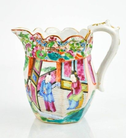 A Chinese Famille Rose jug, painted with figures in a garden, the scalloped and embossed rim painted
