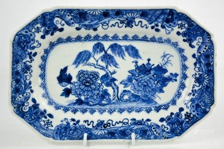 A 19th century Chinese blue and white plate, the centre depicting a table laden with auspicious