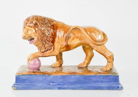 A Victorian Majolica performing lion figure. Standing on rectangular plinth base with mottled glazes