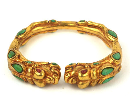 A TIBETAN YELLOW METAL AND TURQUOISE DRAGON BANGLE Having to opposing dragons with cabochon cut