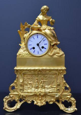 Pendule en bronze doré représentant une scène romantique . Ht 40 cm .