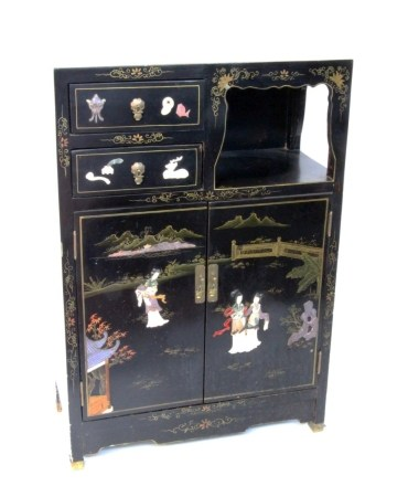A CHINESE LAQUERED CUPBOARD Black lacquered wood with applied figures and flowers made of