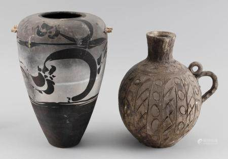 """TWO CERAMIC VESSELS , 1) In seed form with bamboo handles at shoulder. Black and gray matte glaze in Southwestern style. Signed on base. Height 12"""". 2) In jug form with double loop handle. Incised """"X"""" and """"O"""" design a..."""