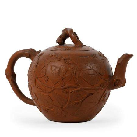 A YIXING EARTHENWARE EGG-SHAPED TEAPOT. ONE HANDLE, FINIAL AND SPOUT. RELIEF DECOR OF GRAPEVINES.