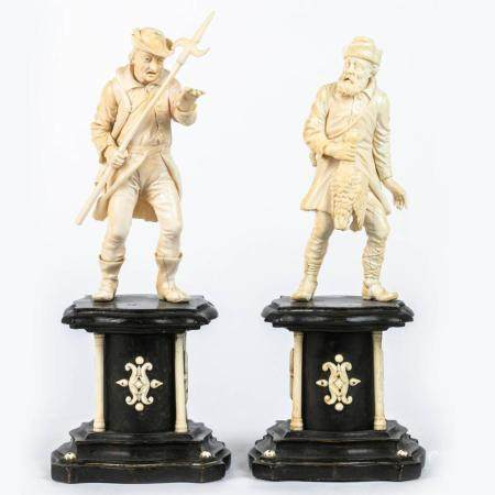 A PAIR OF EARLY 19TH CENTURY GERMAN FIGURES OF HUNTERS IN CARVED IVORY. ON BLACKENED WOODEN BASES. B